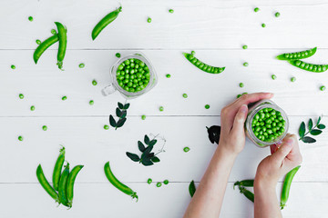 Woman's hands holding full glass jar with green peas on white background near pods of green peas, close-up