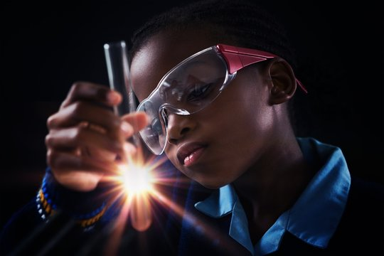 Schoolgirl doing a chemical experiment against black background