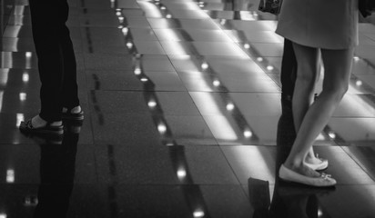 Selective focus on woman legs who stand on black floor in shopping mall or pub. Night scene.