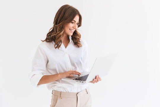 Portrait of adorable smiling woman with long brown hair holding and looking at silver laptop, isolated over white background in studio
