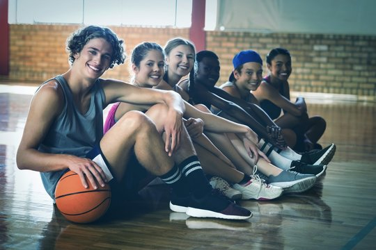 High school kids sitting on the floor in basketball court