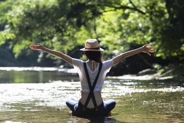 川で寛ぐ女性