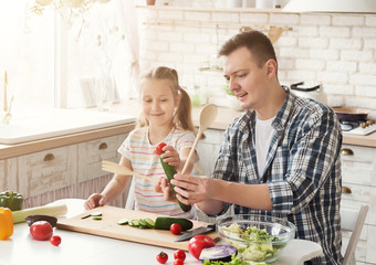 Happy father and his daughter having fun at kitchen