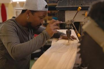 Man using radial drill machine in workshop