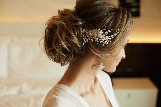Wedding hairstyle of beautiful and fashionable brown-haired model girl in a lace dress, with earrings and jewelry in her hair