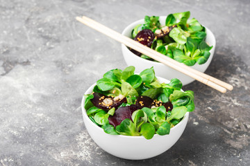 Fresh salad from sprouts of young green lettuce and beets in white bowls in Asian style. The concept of vegetarianism.