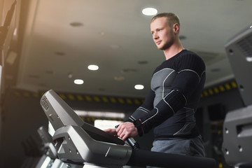 Young man in gym running on treadmill