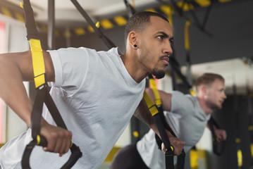Men performing TRX training in gym