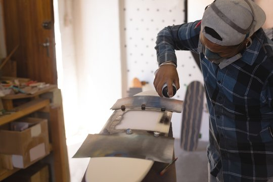 Man spray painting skateboard
