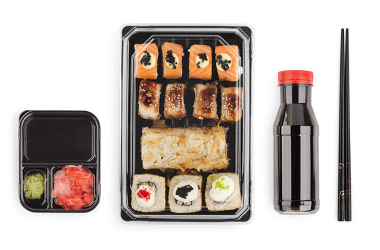 set of sushi rolls in a plastic box, delivered home ready to eat fast healthy food, isolated on white top view