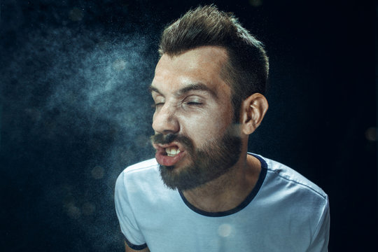 Young handsome man with beard sneezing, studio portrait