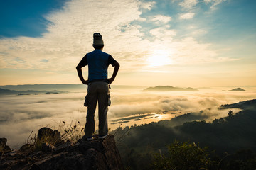 Silhouette man standing on top of the mountain watching the sun rise with fog