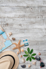 Summer vacation background with copy space,seashells,starfish,map,hat,map and polaroid photo of beach