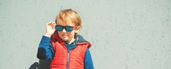 Stylish kid in trendy sunglasses. Kids fashion. Cute little blondy boy in red jacket standing over grey wall outdoors in sunny day. Autumn, spring kids fashion. Kids sunglasses. Hipster style.
