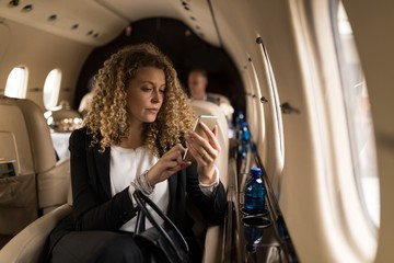 Businesswoman using mobile phone in private jet