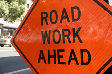 diamond shaped orange red reflector street sign that reads road work ahead