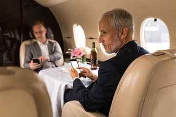 Businessman using mobile phone in private jet
