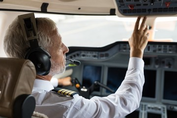 Male pilot pushing button in cockpit