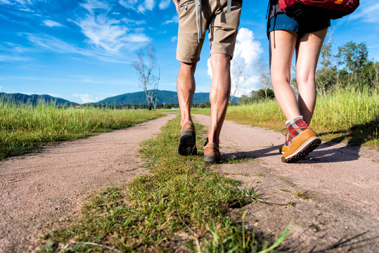 Close up of lower legs of two travelers walking along path in nature. Hiking and Camping concept. Backpacker an Tourist concept. Outdoors activity and adventure theme.