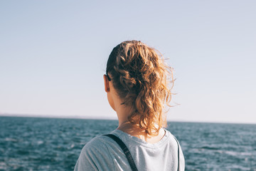 Candid photo of young woman's head looking at the sea