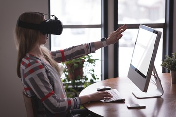 Female executive using virtual reality headset with computer at
