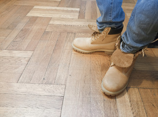 man with blue jeans and work boots on wood floor