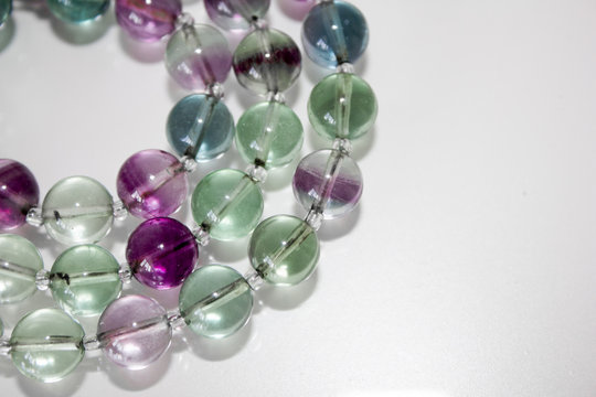 close up macro natural fluorite gem beads isolated on white background