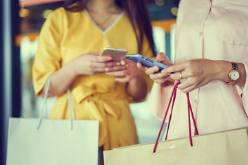 close up beautiful asian woman holding bag and smartphone while finish shopping in mall