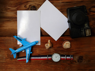 Flat lay photo with toy airplane, vintage camera, watches and mockup cards on wooden table. Summer vacation concept