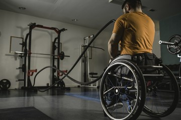 Handicapped man on wheelchair exercising with battle ropes
