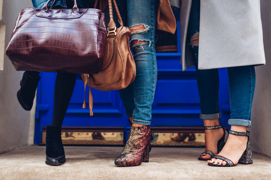 Three women wearing stylish shoes and accessories outdoors. Beauty fashion concept. Ladies holding female handbags