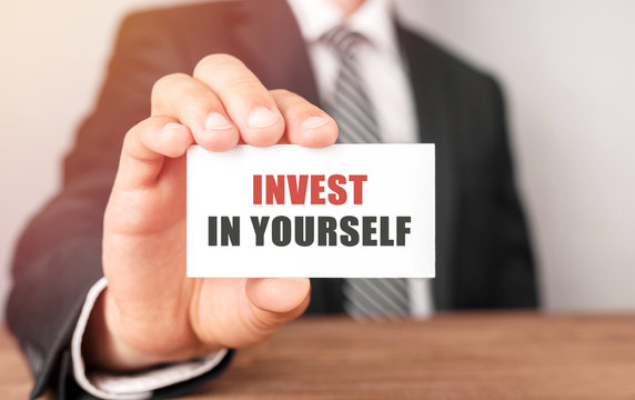 Businessman holding a card with text Invest in Yourself