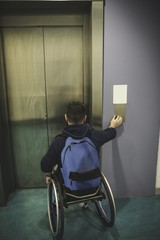 Handicapped man pressing button of elevator