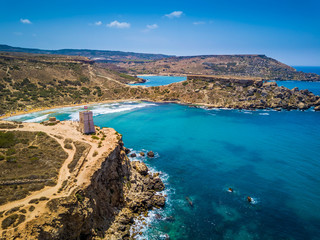 Ghajn Tuffieha, Malta - Beautiful Ghajn Tuffieha Bay, Ghajn Tuffieha Watch Tower and Riviera beach from above on a bright summer day with Gnejna Bay and blue sky at background