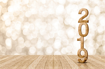 2019 happy year wood number in perspective room with sparkling bokeh wall and wooden plank floor.copy space for display of product or text.