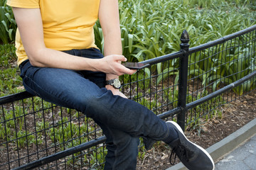 young man in blue jeans and yellow t shirt using his cellphone