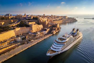 Photo sur Aluminium Europe Méditérranéenne Valletta, Malta - Cruise ship sailing into Grand Harbor at sunrise with the ancient city of Valletta at background