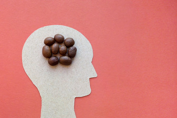 Cardboard head coffee bean is the symbol of the brain red background, copy paste