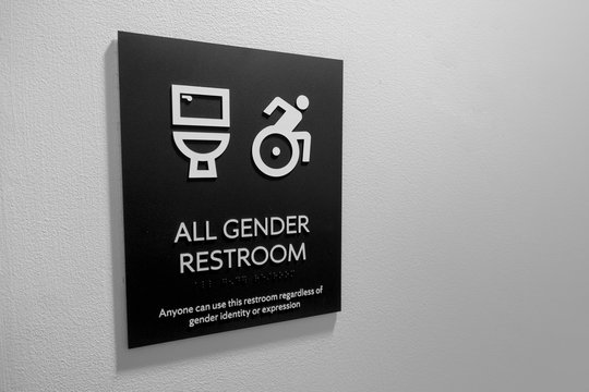 restroom sign with wheelshair access with toilet, wheelchair person icons and text reading all gender restroom