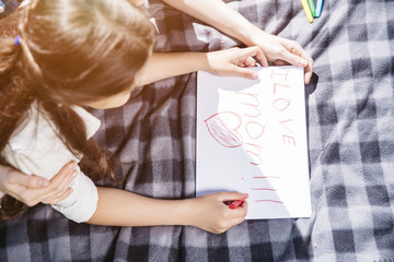 Sweet and nice picture of girl lying on blanket and drawing. She is using red-colored pencil. She has written on a piece pf paper I love mom .