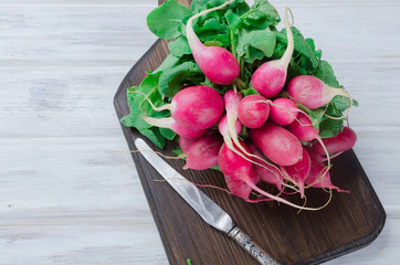 bunch of radishes with leaves on a wooden table