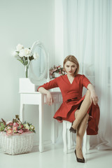 Woman in red dress. sexy woman grooming in morning at mirror. bedroom decor for elegant woman. confident and beautiful. Be A Woman A Man Needs.