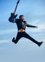 Motion and fun concept. Happy young man jumping in air and playing guitar over blue sky and clouds background