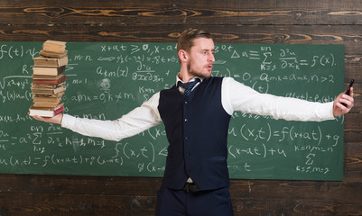 Man teacher balancing in hands pile of books and smartphone as symbol analog and digital information storages. Modern against outdated. Teacher formal wear, chalkboard background. Balance concept