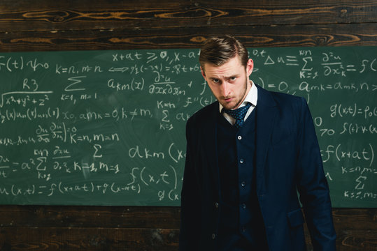 Talented mathematician. Genius solved mathematics problem.Teacher smart student intrested math physics exact sciences. Man formal wear classic suit looks smart, chalkboard with equations background