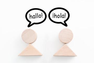Figuren mit Begrüßung in Deutsch und Spanisch in Sprechblasen