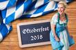 """junge Frau im Dirndl vor Hintergrund mit bayrischem Rautenmuster und Aufschrift """"Oktoberfest 2018"""""""