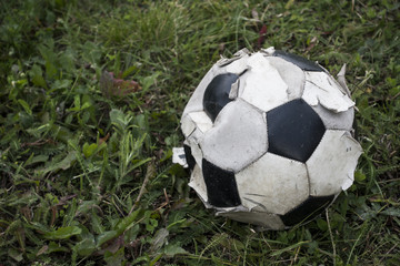 Old black and white soccer ball (Football) on green grass