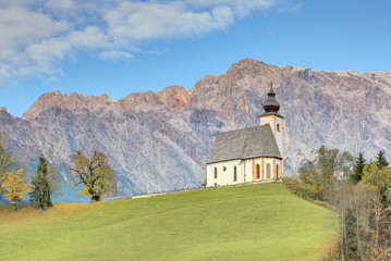 A church standing high on a grassy hilltop with a rocky mountain range in background~ Autumn scenery of St. Nikolaus Parish Church of Dienten Village at the foothill of Hochkoenig Mountains in Austria
