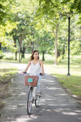Asian woman ride bicycle in summer park